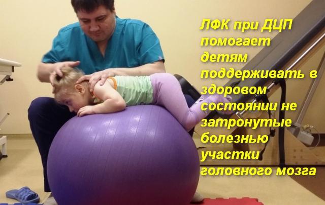 врач помогает ребенку делать движения на фитболе
