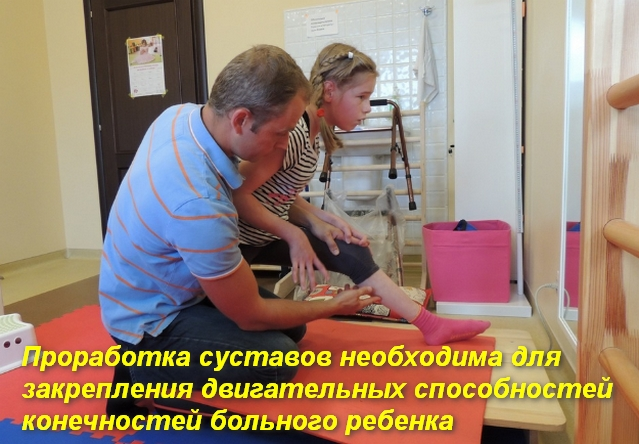 врач помогает ребенку сделать движение ногой