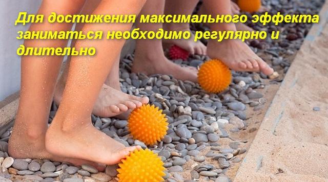 детские ноги катают мячик с шипами