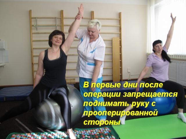2 женщины сидя на фитболе поднимают руку под присмотром врача