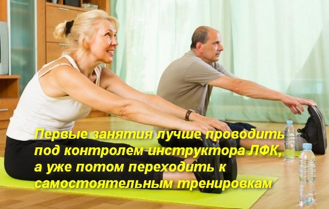 мужчина и женщина сидя на полу выполняют наклон вперед