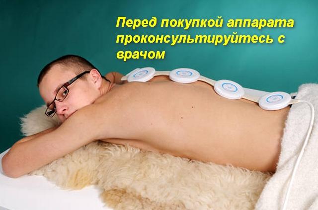 на спине у мужчины аппарат для магнитной терапии