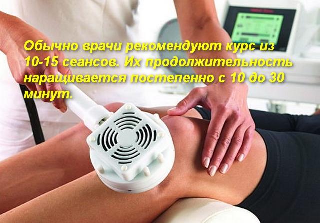 врач делает пациенту магнитотерапию на колено