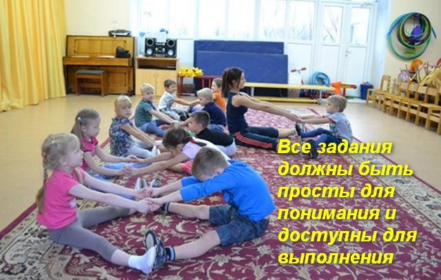 дети сидя на полу в парах делают упражнение